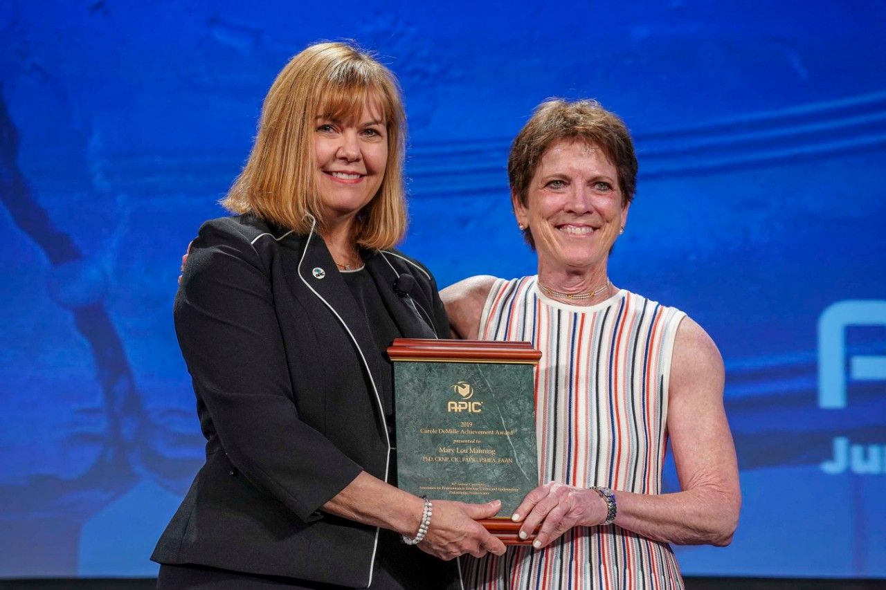 Dr. Mary Lou Manning (right) receives the Carole DeMille Achievement Award from APIC president Karen Hoffmann.
