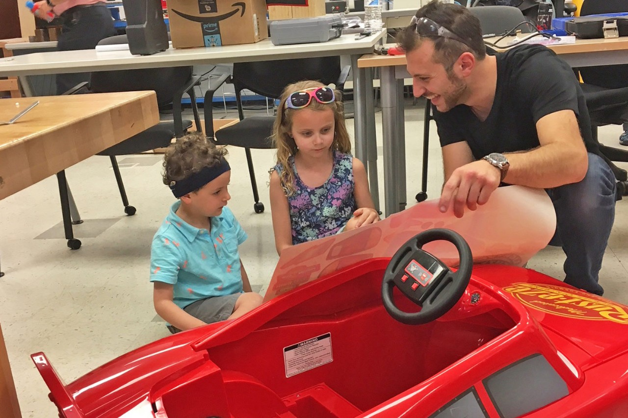 Student working on the design of a car with some help from children