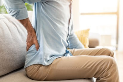 White man sitting on couch with back pain
