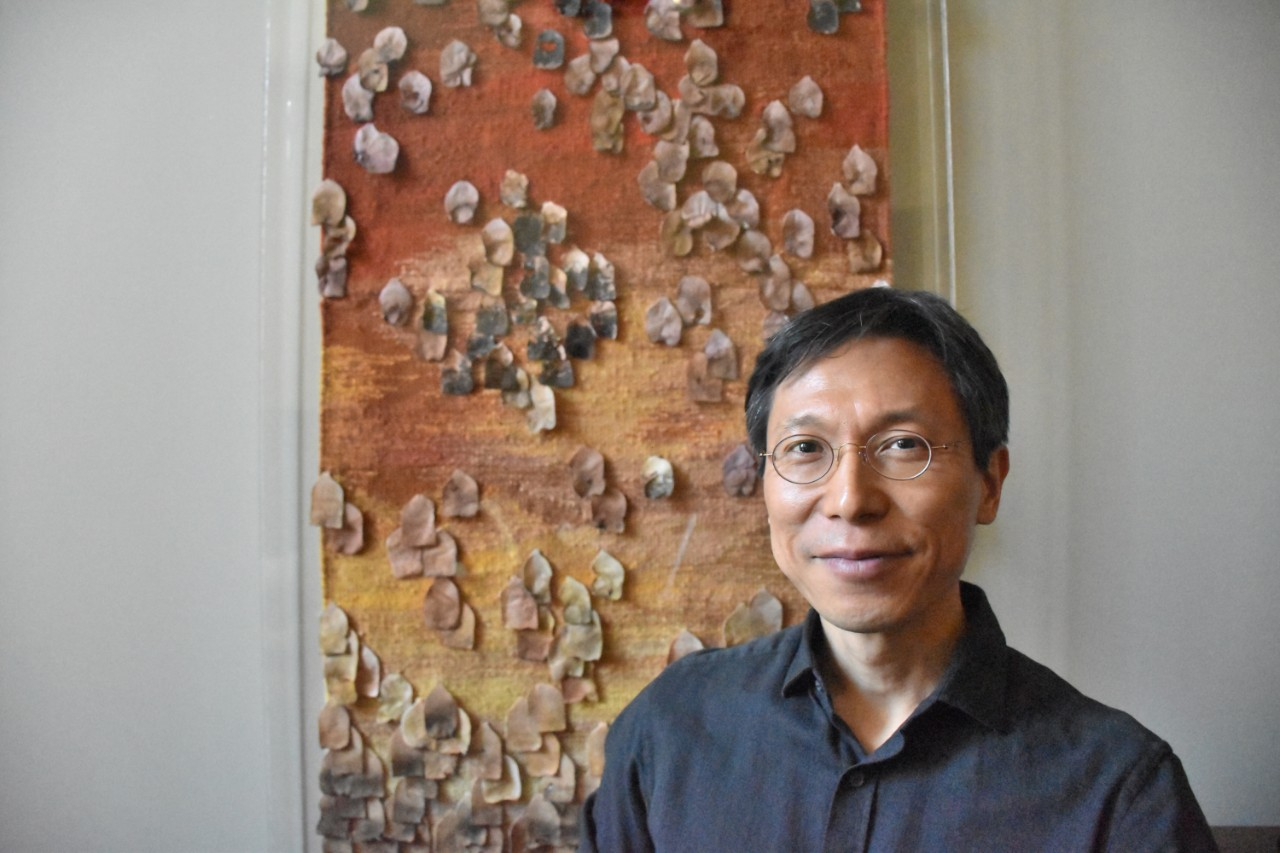 Man sitting in front of artwork.