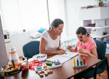 white woman working with a white woman with an intellectual disability using many props and toys.