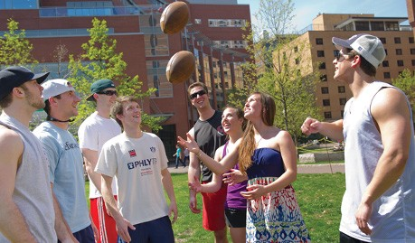 Students throwing footballs on campus